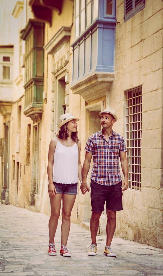 Pares jovenes que caminan en calle vieja en La Valeta, Malta fotografía de archivo libre de regalías