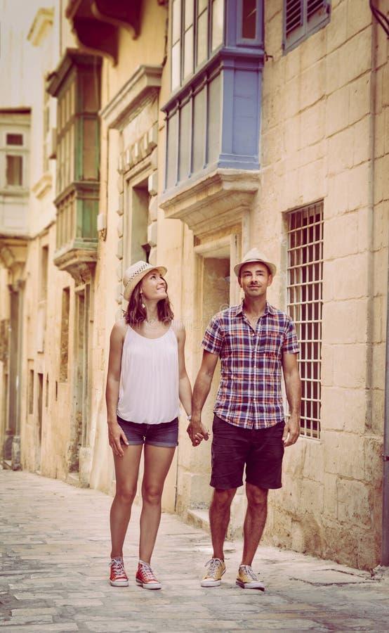 Pares jovenes que caminan en calle vieja en La Valeta, Malta imagen de archivo libre de regalías