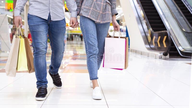 Pares jovenes que caminan en el centro comercial, cosecha imagen de archivo