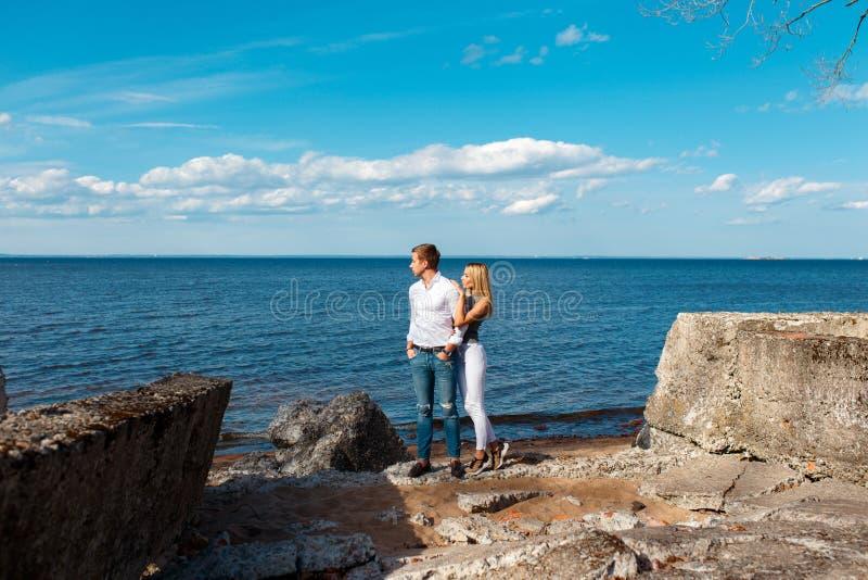 Pares jovenes que caminan en la playa imagen de archivo