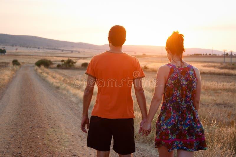Pares jovenes que caminan en la puesta del sol imagen de archivo libre de regalías
