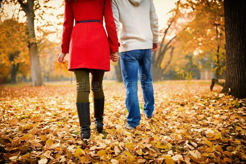 Pares jovenes que caminan en parque en otoño imagenes de archivo