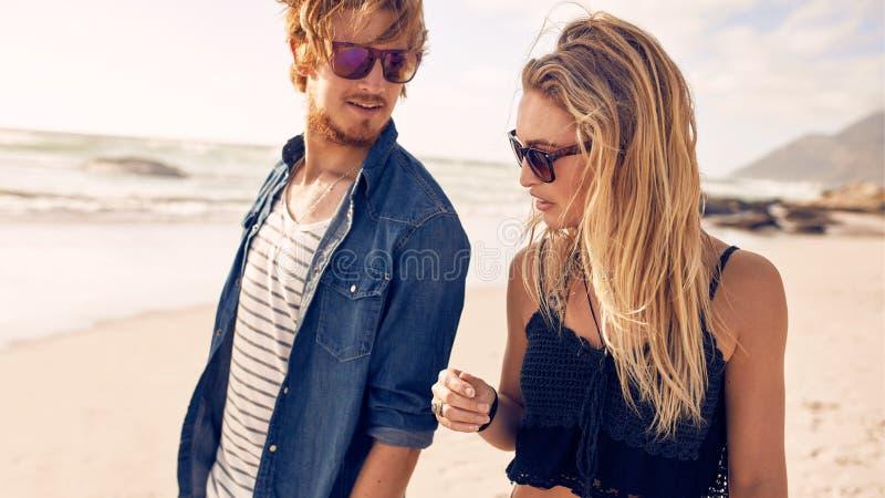 Pares jovenes que caminan a lo largo de una playa imagenes de archivo