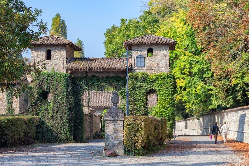 Pares jovenes que caminan a lo largo del castillo de Grazzano Visconti fotos de archivo libres de regalías