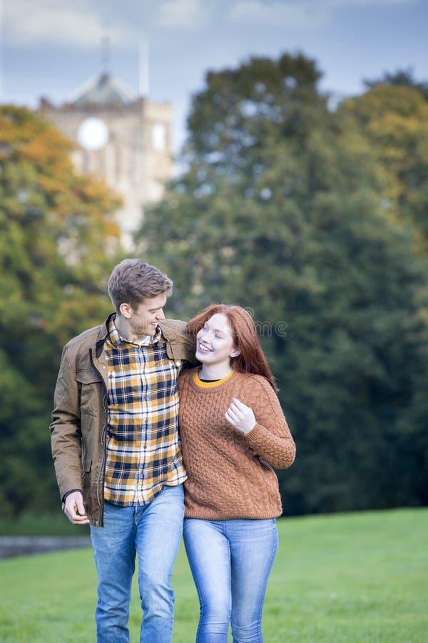 Pares jovenes que caminan a través de un parque imagenes de archivo