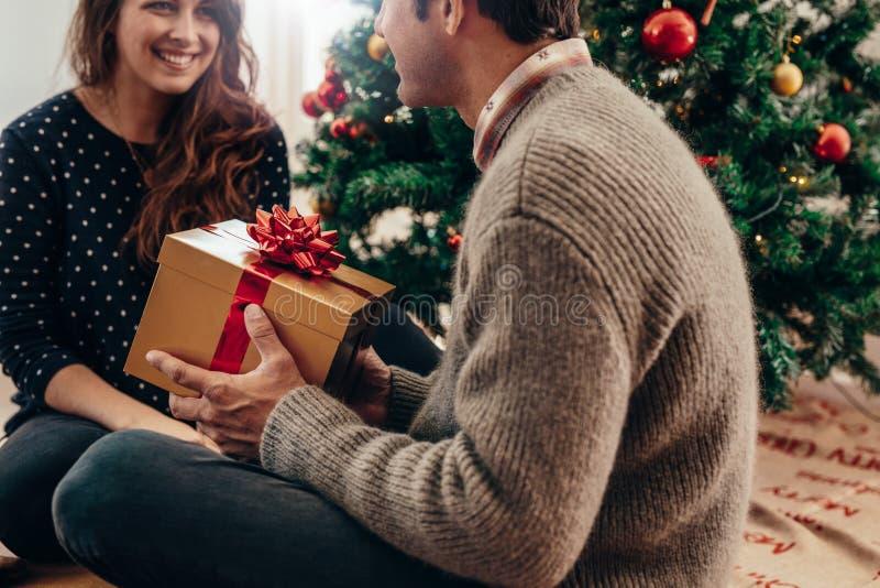 Pares jovenes que celebran la Navidad en casa foto de archivo