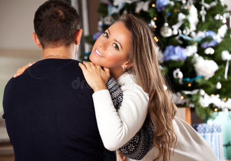 Pares jovenes que celebran la Navidad en casa fotografía de archivo