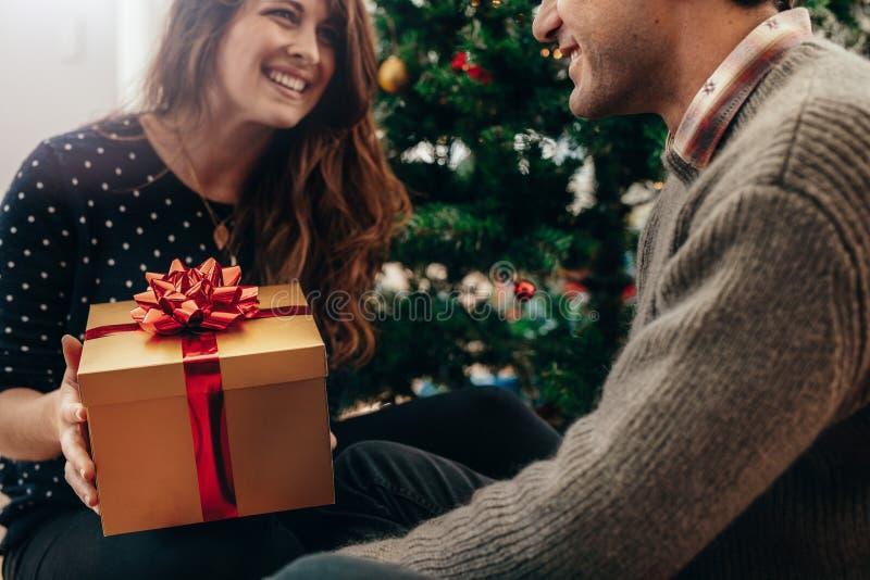Pares jovenes que celebran la Navidad intercambiando los regalos fotografía de archivo