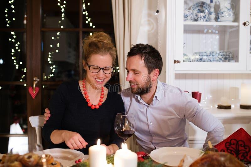 Pares jovenes que celebran la Navidad junta en casa imagen de archivo libre de regalías