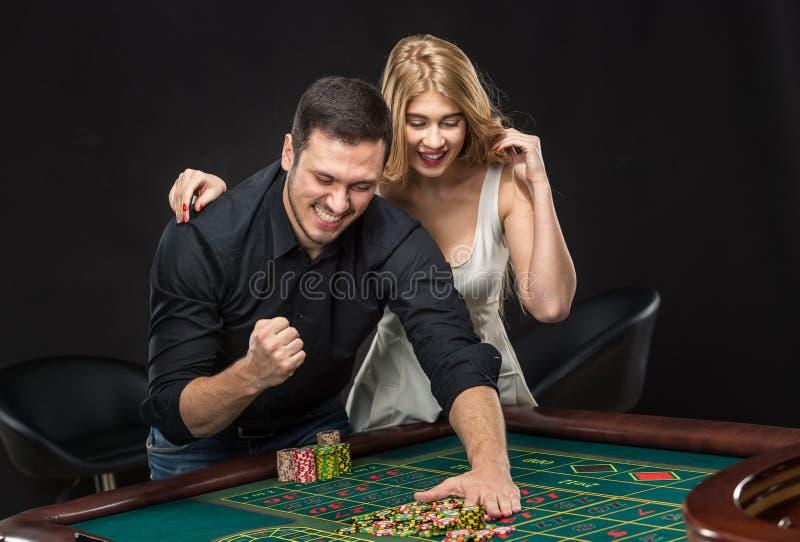 Pares jovenes que celebran triunfo en la tabla de la ruleta en casino foto de archivo