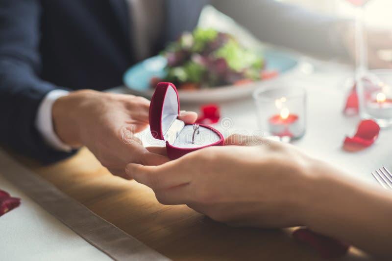 Pares jovenes que cenan romántico en el restaurante que sostiene el primer del anillo de la oferta imágenes de archivo libres de regalías