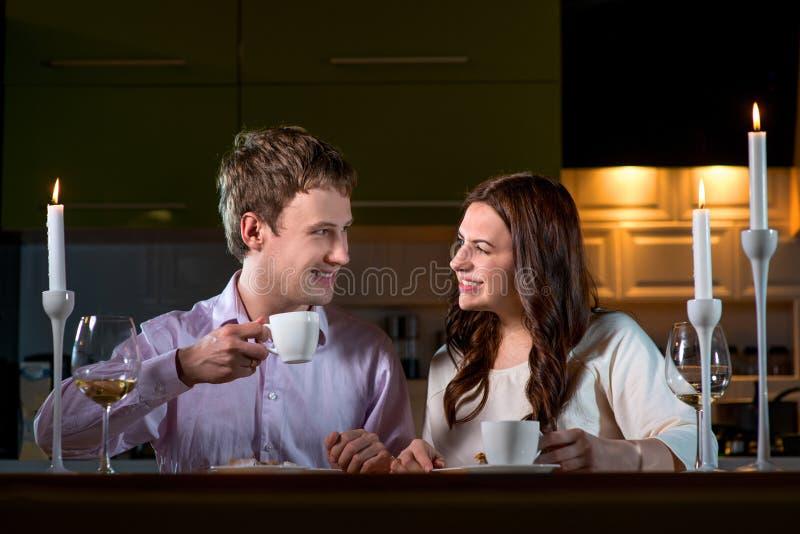 Pares jovenes que cenan romántico en la tabla de cena en casa imagenes de archivo