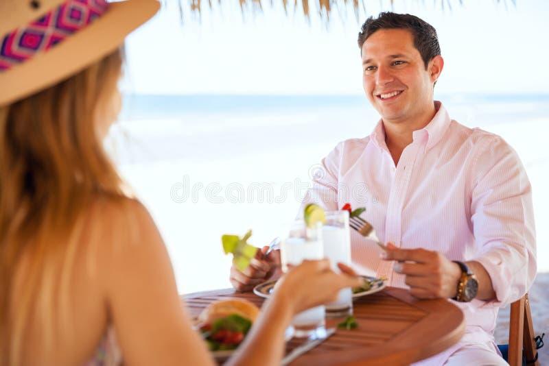 Pares jovenes que comen el almuerzo en la playa fotos de archivo