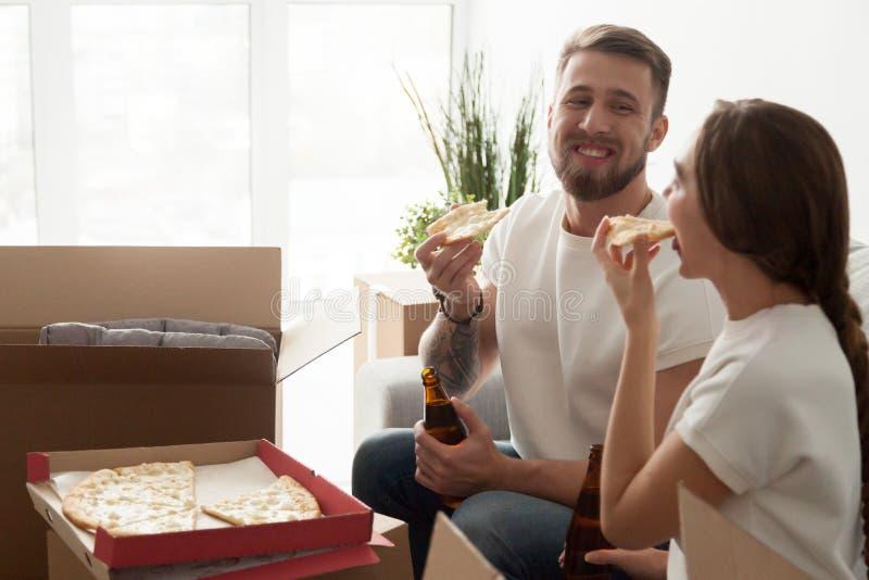 Pares jovenes que comen el partido del estreno de una casa de la pizza, celebrando la mudanza fotos de archivo libres de regalías