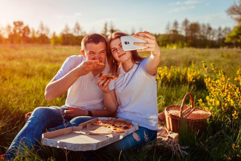 Pares jovenes que comen la pizza exterior y que toman el selfie Mujer y hombre que tienen comida campestre en la puesta del sol I imagen de archivo libre de regalías