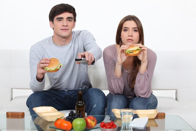Pares jovenes que comen las hamburguesas fotografía de archivo libre de regalías