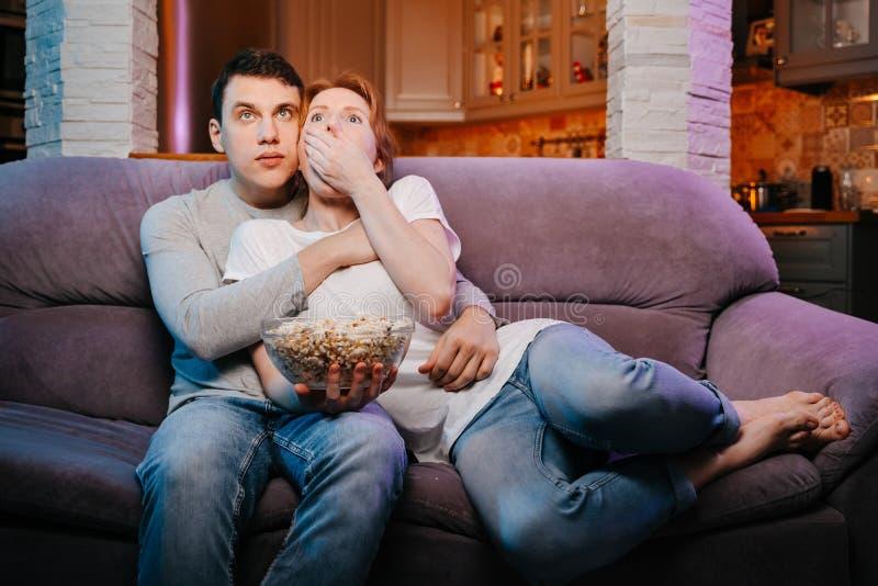 Pares jovenes que comen las palomitas y que miran una película en casa en el sofá, asustado fotos de archivo libres de regalías