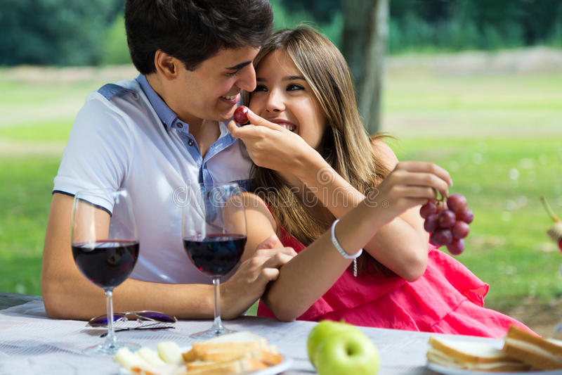 Pares jovenes que comen las uvas en comida campestre romántica en campo imágenes de archivo libres de regalías