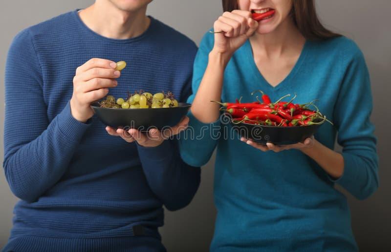Pares jovenes que comen las uvas y el chile en fondo gris imagen de archivo