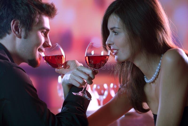 Pares jovenes que comparten un vidrio de vino rojo en el restaurante, celebrat imagenes de archivo