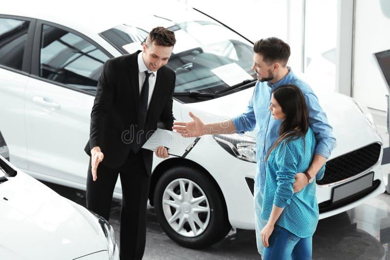 Pares jovenes que compran el nuevo coche fotos de archivo