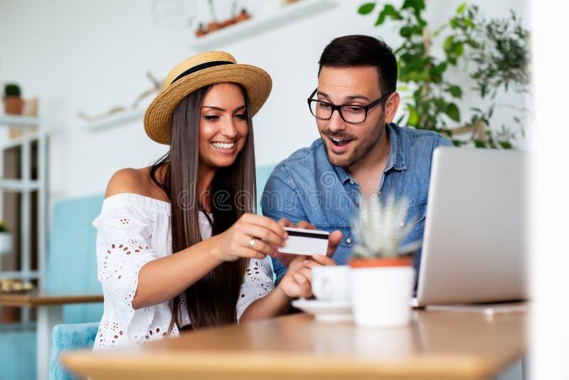 Pares jovenes que compran en línea con la tarjeta de crédito y el ordenador portátil en una cafetería - Imagen foto de archivo libre de regalías
