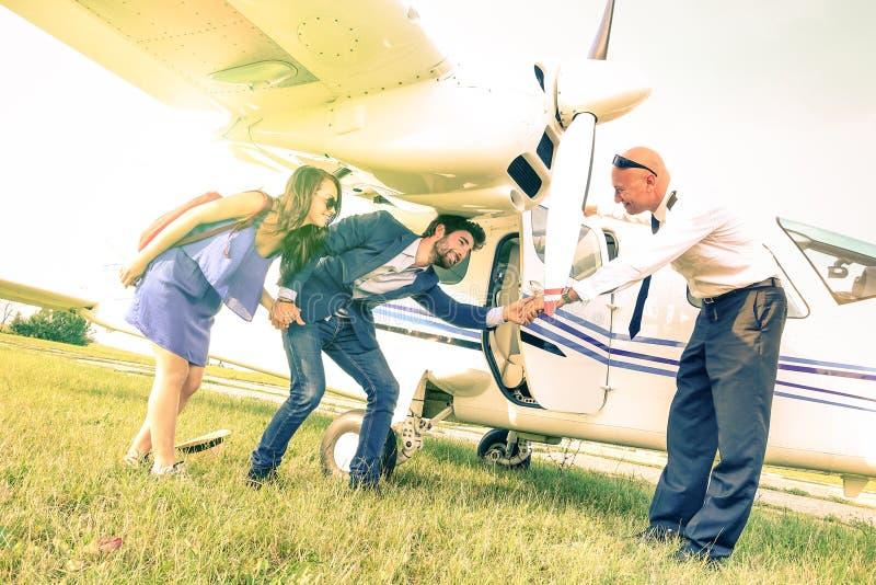 Pares jovenes que consiguen en el aeroplano ligero con el capitán imagenes de archivo