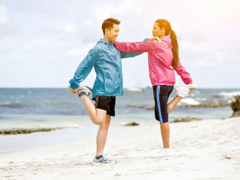 Pares jovenes que consiguen listos para correr en la playa fotos de archivo
