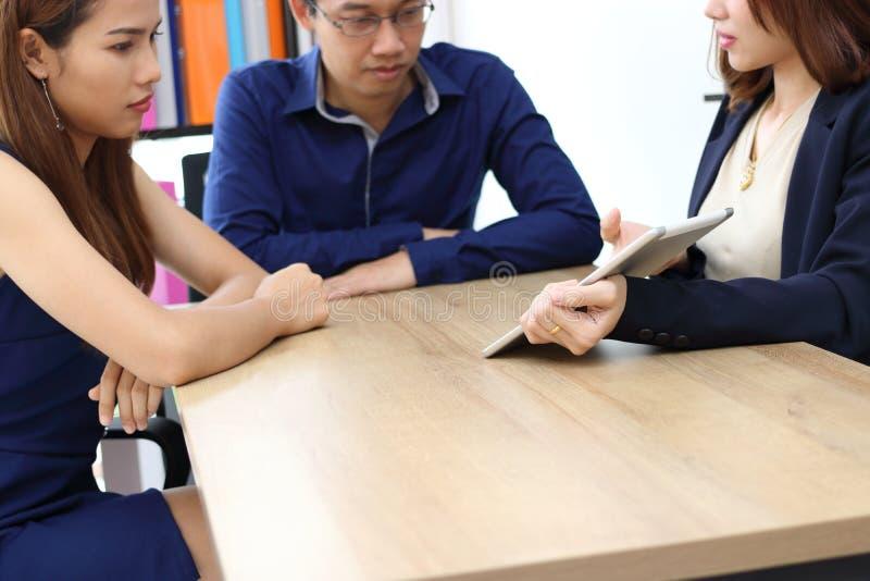 Pares jovenes que consultan con el consejero financiero en oficina imagen de archivo