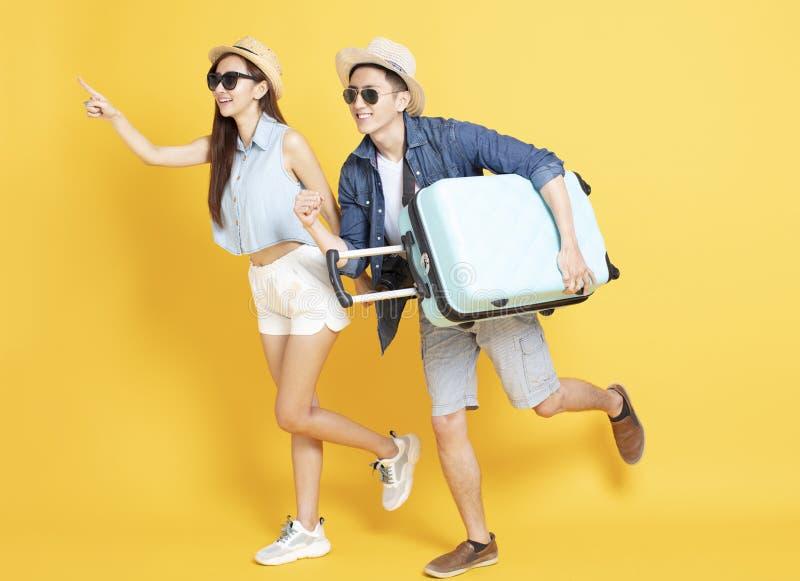 pares jovenes que corren con equipaje del viaje imagen de archivo libre de regalías