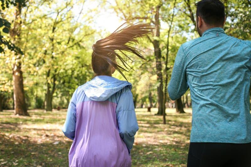 Pares jovenes que corren junto en parque Ejercicio de la gente joven imagenes de archivo
