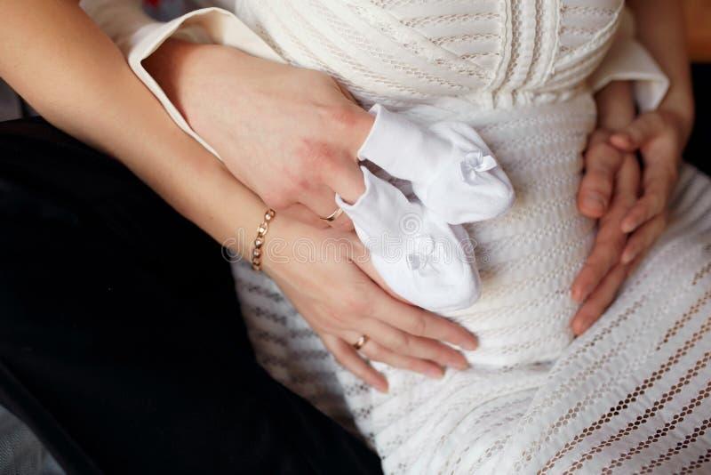 Pares jovenes que cuentan con al bebé que abraza el estómago Embarazo y concepto de la gente foto de archivo libre de regalías