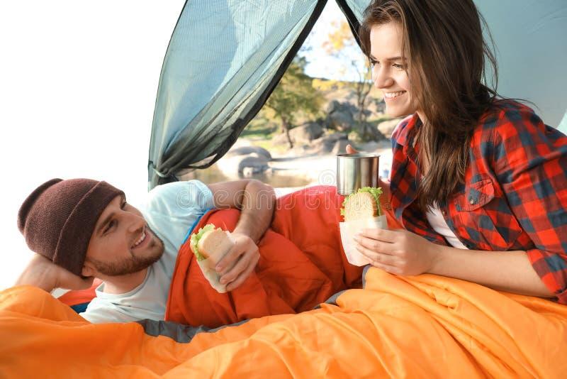 Pares jovenes que desayunan en sacos de dormir dentro fotos de archivo libres de regalías