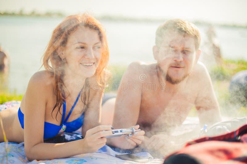 Pares jovenes que descansan sobre la playa, cigarrillo electrónico que fuma imágenes de archivo libres de regalías