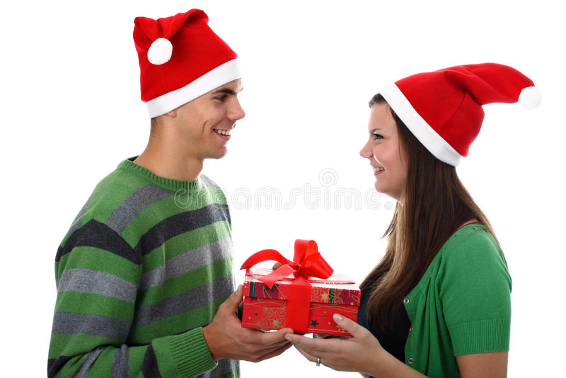 Pares jovenes que desgastan los sombreros de Santa aislados en blanco fotos de archivo libres de regalías