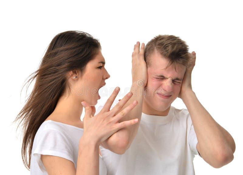 Pares jovenes que discuten con uno a la griterío de grito de la mujer en h foto de archivo