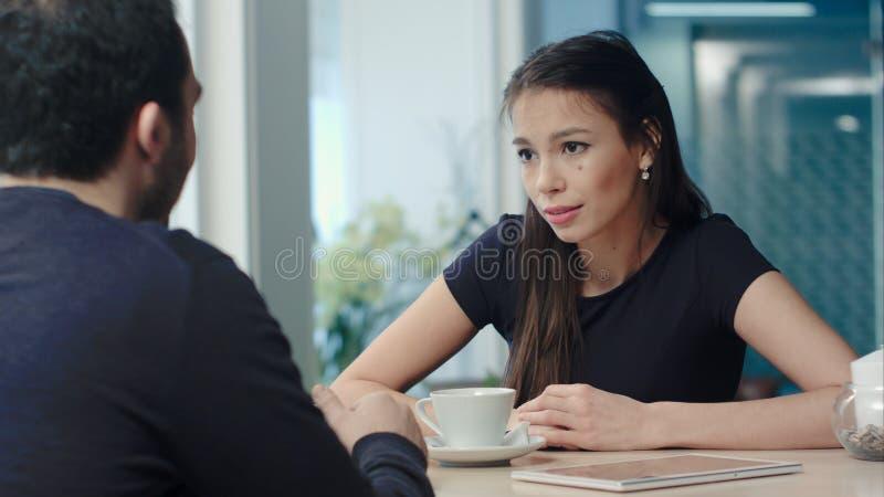 Pares jovenes que discuten en un café fotos de archivo