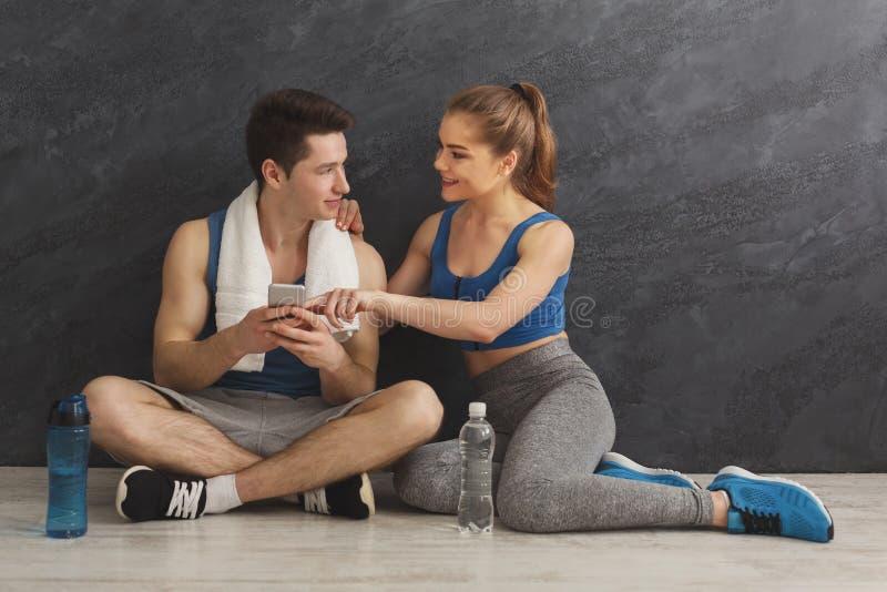 Pares jovenes que discuten plan del entrenamiento en el gimnasio fotos de archivo