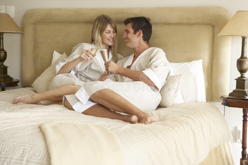 Pares jovenes que disfrutan de Champán en dormitorio imagen de archivo