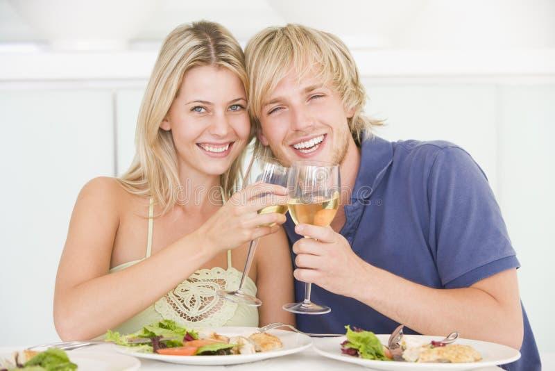 Pares jovenes que disfrutan de la comida imagen de archivo