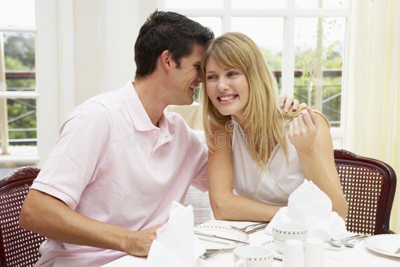 Pares jovenes que disfrutan de la comida del hotel imagen de archivo