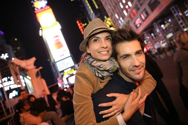 Pares jovenes que disfrutan de la igualación en Times Square imagen de archivo