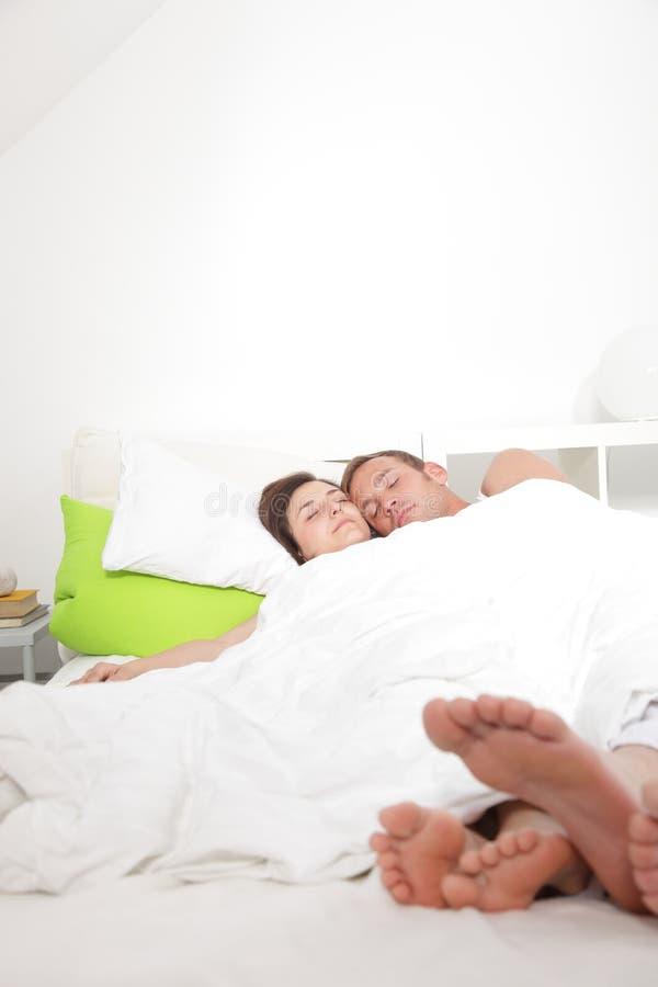 Pares jovenes que disfrutan de un día relajante en cama imagen de archivo