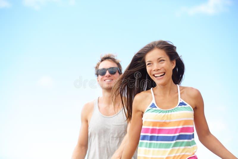 Pares jovenes que disfrutan del funcionamiento de risa de la diversión de la playa foto de archivo