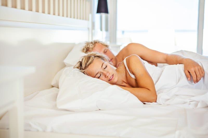 Pares jovenes que duermen en cama imagen de archivo