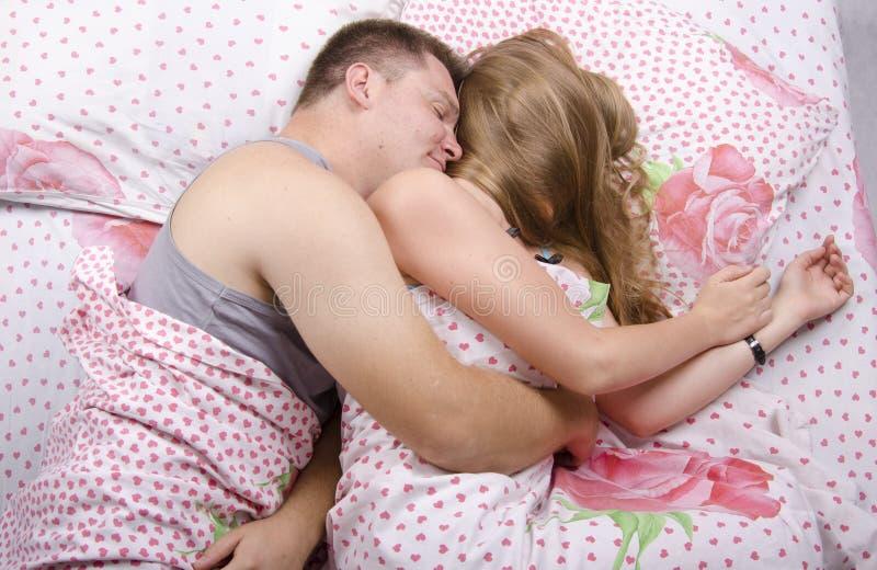 Pares jovenes que duermen en cama imagen de archivo libre de regalías