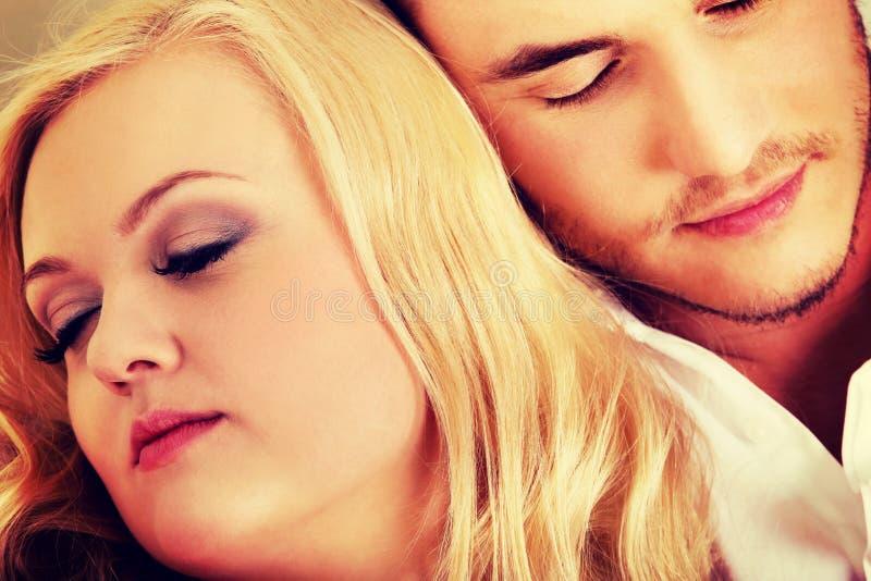 Pares jovenes que duermen en el sofá debajo de la manta imagen de archivo libre de regalías