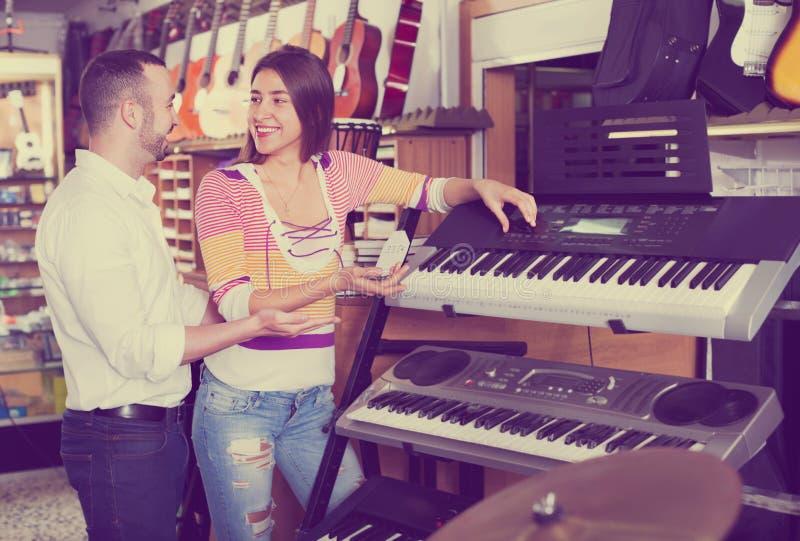 Pares jovenes que eligen el sintetizador en tienda de la música fotografía de archivo libre de regalías