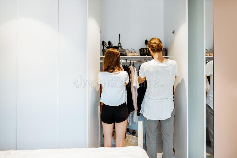 Pares jovenes que eligen la ropa en el dormitorio en casa fotografía de archivo libre de regalías