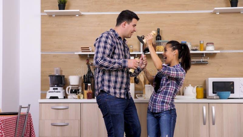 Pares jovenes que engañan alrededor en su cocina mientras que prepara la cena fotos de archivo libres de regalías